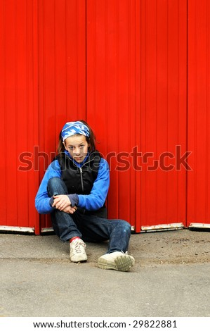 portrait of modern child leaning against red wall - stock photo