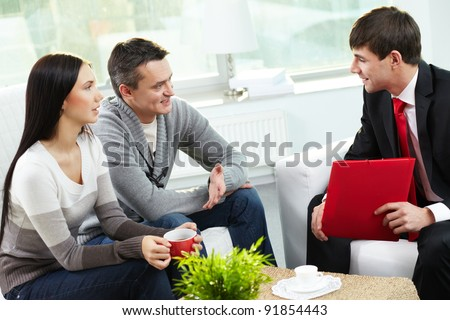 Portrait of modern couple talking to manager while discussing conditions of mortgage - stock photo