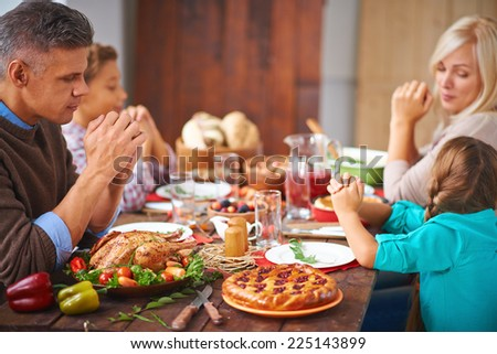 Portrait of modern family of four sitting at festive table and praying - stock photo