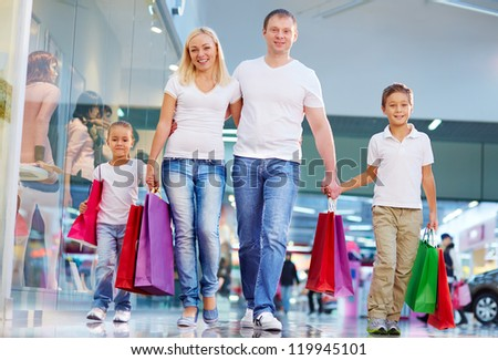 Portrait of modern family with paperbags walking in the mall