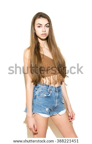 Portrait of modern fashionable boho styled young woman with long hair in  trendy summer outfit. Fit model girl in blue denim shorts and brown crochet crop top. Isolated on white, medium retouch. - stock photo