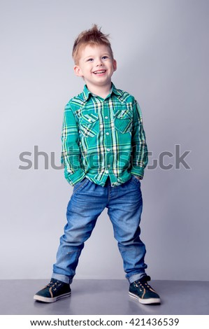 Portrait of modern fashionable  boy posing on a grey background. He is dressed in a checked green shirt  blue jeans and green sneaker. Studio shot    - stock photo