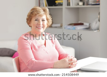 Portrait of modern grandmother with laptop sitting at desk. - stock photo