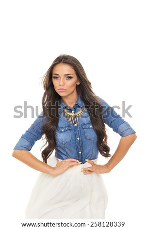 Portrait of modern young confident fashionable Latina woman in trendy denim shirt and white skirt posing looking at camera with hands on hips. Retouched, no color filters. - stock photo