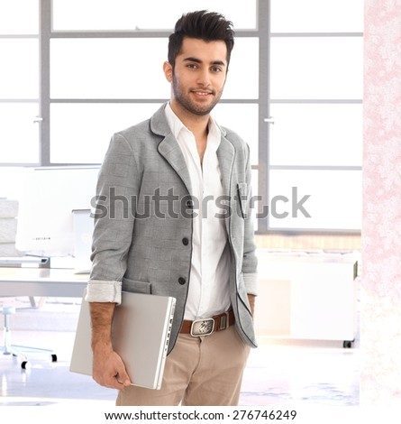 Portrait of modern young handsome arabian businessman at office, smiling. - stock photo