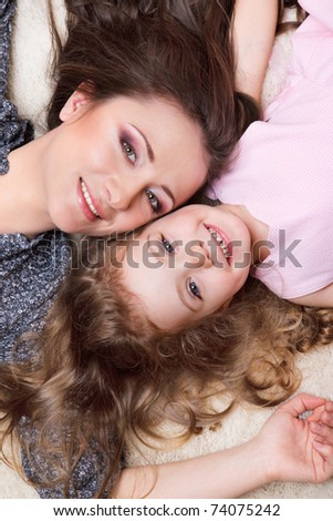 Portrait of mom and curly girl lying close to each other - stock photo