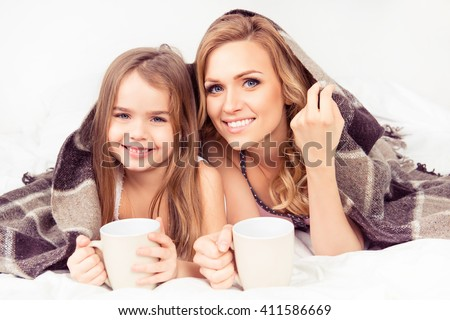 Portrait of mom and daughter basking under plaid with cups of hot milk - stock photo