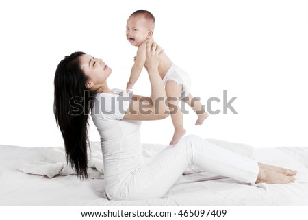 Portrait of mom lifting her cute baby into the air, isolated on white background