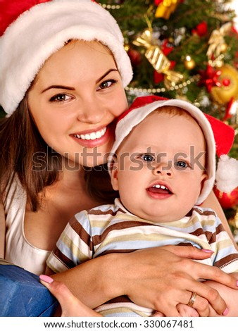 Portrait of mom wearing Santa hat holding  baby son  under Christmas tree.