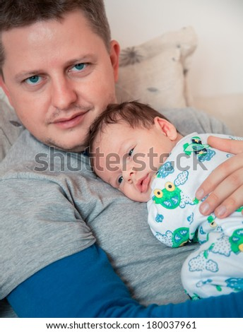 Portrait of 1 month old baby boy in his daddy's arms, almost asleep at home.