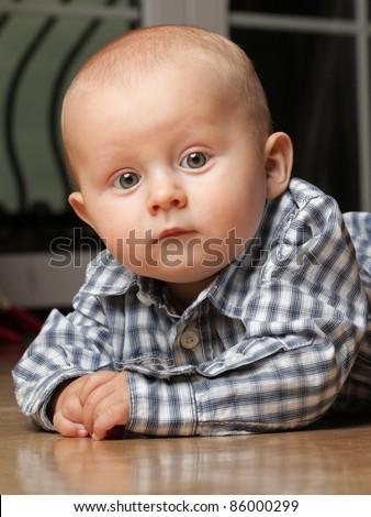 portrait of 6 months boy, male child sitting on floor - stock photo