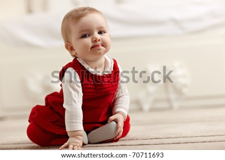 portrait of 6 months female child sitting on floor in red clothes and looking at camera. Horizontal shape, front view, copy space - stock photo