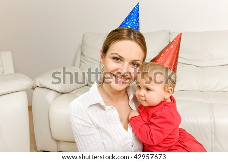 Portrait of mother and adorable baby celebrating birthday or New Year - stock photo
