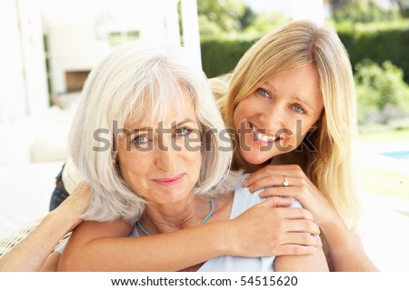 Portrait Of Mother And Adult Daughter Relaxing On Sofa - stock photo