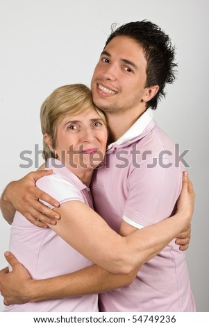 Portrait of mother and adult  son hugging and smiling together and wearing pink t shirts,they are really family,over gray background - stock photo