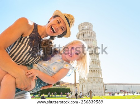 Portrait of mother and baby girl in front of leaning tower of pisa, tuscany, italy - stock photo