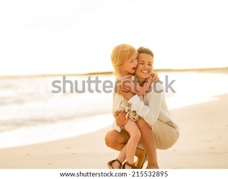 Portrait of mother and baby girl on the beach in the evening - stock photo