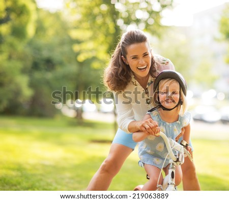 Portrait of mother and baby girl with bicycle - stock photo