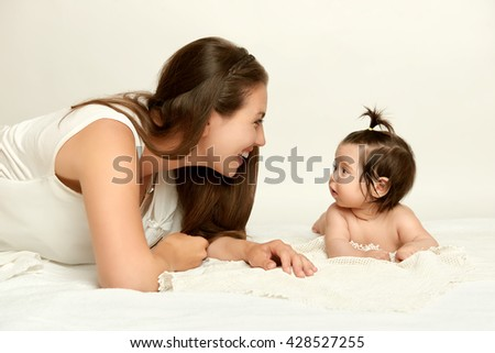 portrait of mother and baby having fun, lie on white, yellow toned - stock photo