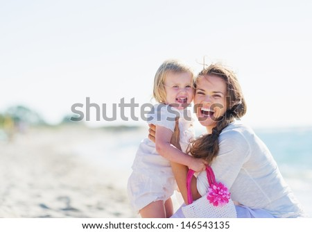 Portrait of mother and baby on sea shore - stock photo