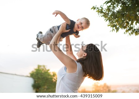 Portrait of mother and baby outdoor on the sunset. Mom and her one years old baby boy have fun on the park. Mum throws kid and child smiling and laughing - stock photo
