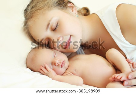 Portrait of mother and baby sleep together on the bed at home - stock photo