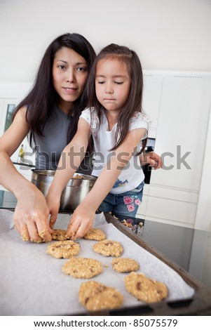 Portrait of mother and child in kitchen making cookies - stock photo