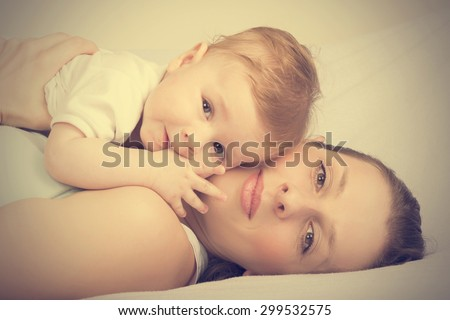 Portrait of mother and child laughing, vintage effect added