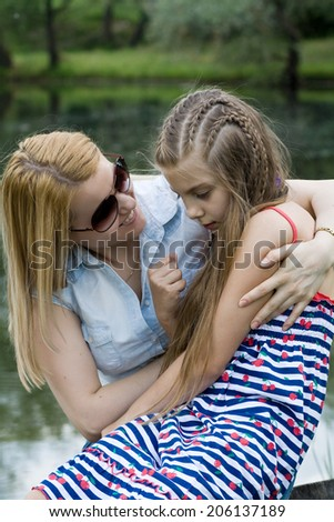 Portrait of mother and daughter against the nature view. Leisure time of happy family. - stock photo