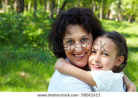Portrait of mother and daughter embracing during summer vacation