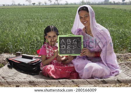 Portrait of mother and daughter holding a writing slate with alphabets written on it - stock photo