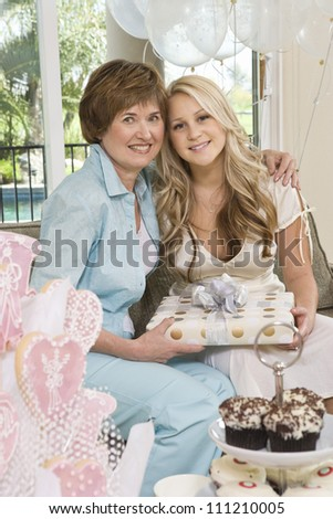 Portrait of mother and daughter holding gift at  party - stock photo