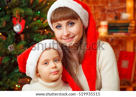 portrait of mother and daughter in caps of Santa Claus
