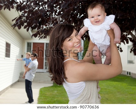 Portrait of mother and daughter in front of house with father and son in background - stock photo
