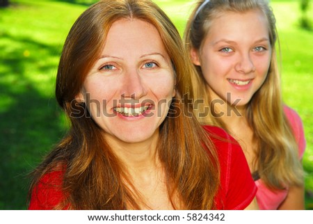 Portrait of mother and daughter in summer park - stock photo