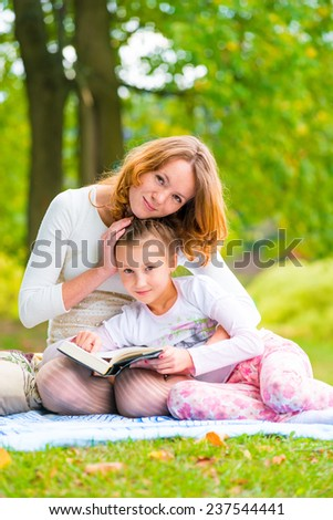 portrait of mother and daughter in the summer park - stock photo