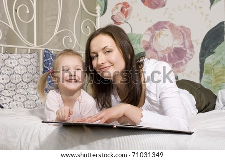 portrait of mother and daughter laying in bed and  reading book - stock photo