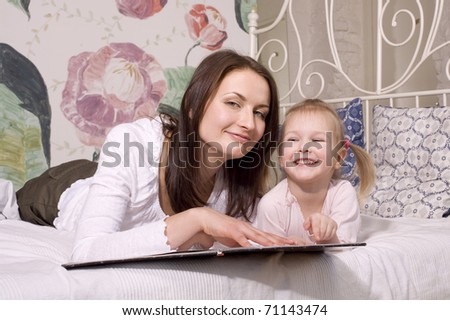 portrait of mother and daughter laying in bed  reading book and hugging - stock photo