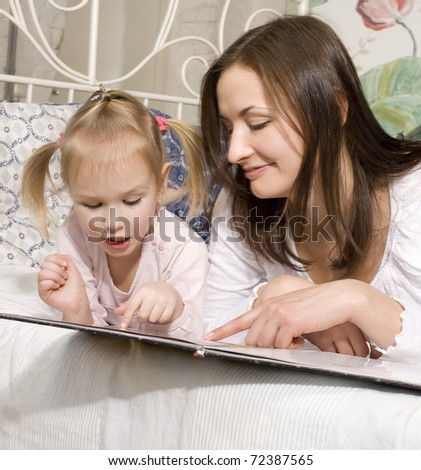 portrait of mother and daughter laying in bed  reading book and talking - stock photo