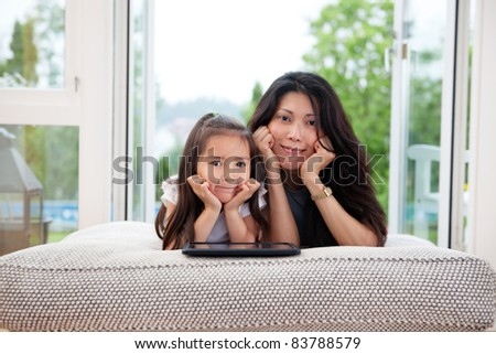 Portrait of mother and daughter lying on couch with digital tablet - stock photo
