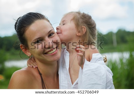Portrait of mother and daughter outdoors forest river grass - stock photo