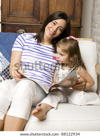 Portrait of mother and daughter playing in bed