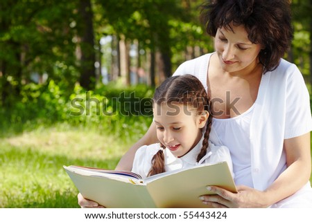 Portrait of mother and daughter reading book on summer day