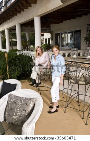 Portrait of mother and daughter relaxing on patio - stock photo