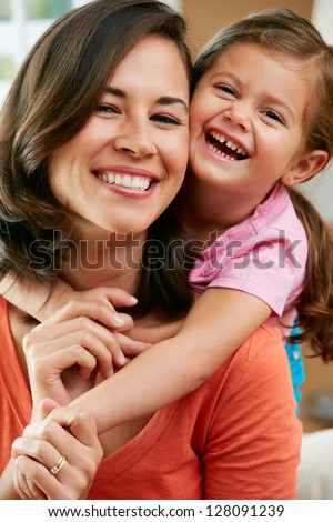 Portrait Of Mother And Daughter Sitting On Sofa At Home - stock photo