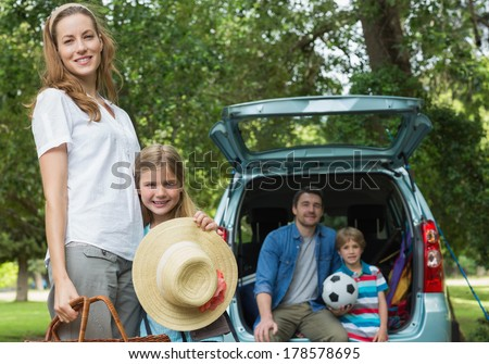Portrait of mother and daughter with father and son sitting in car trunk