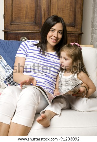 Portrait of mother and daughter with journal reading and hugging