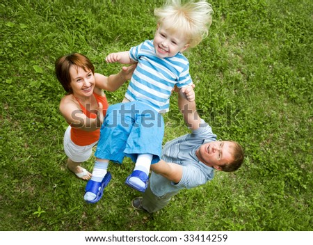 Portrait of mother and father playing with son - stock photo