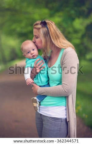 portrait of mother and her beautiful baby boy in park - stock photo