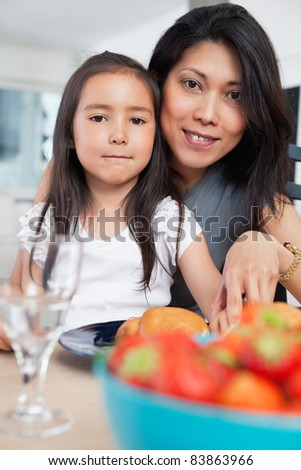 Portrait of mother and her cute daughter sitting at table - stock photo
